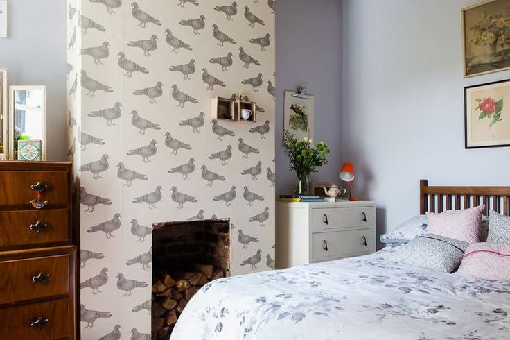 Bedroom with floral bedding, thornback & peel pigeon wallpaper, vintage floral paintings & vintage chest of drawers.