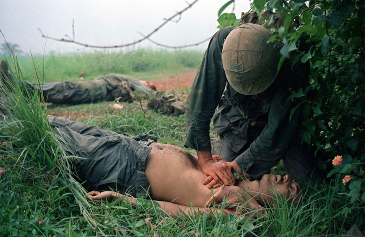 A corpsman (an enlisted soldier trained to give first aid and minor medical treatment) tries to help wounded Marines in Vietnam in Sept. 1966. Horst Faas / AP ~ Vietnam War