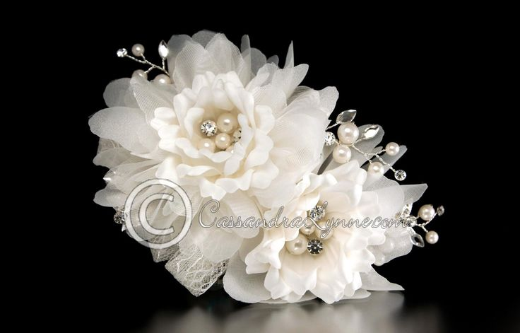 A soft and wonderful bridal hair flower to accent your wedding hair style. Two ivory, faux silk and organza flowers are accented by loops of lace ribbon, sprays of marquise rhinestones and ivory pearl                                                                                                                                                      More