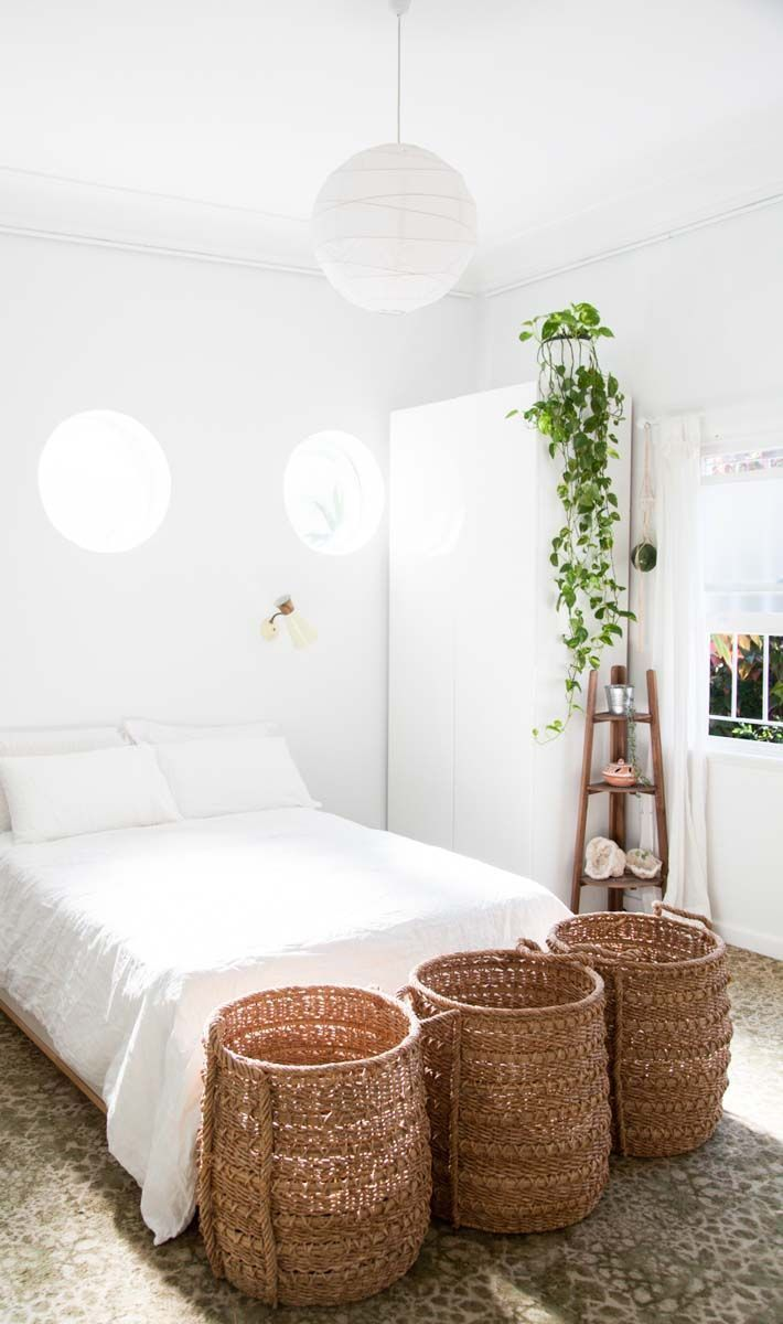 Minimalist white bedroom with woven baskets and round paper lantern.