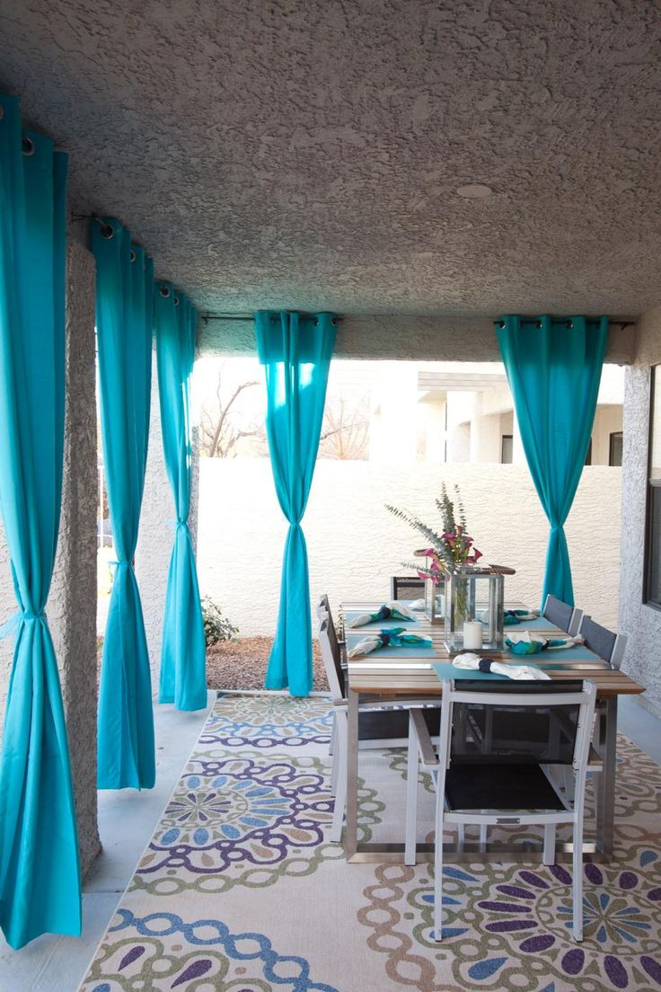 Jonathan turned the bare back porch into an outdoor dining area perfect for entertaining. Hanging fabric panels add shade, privacy and color to the space.