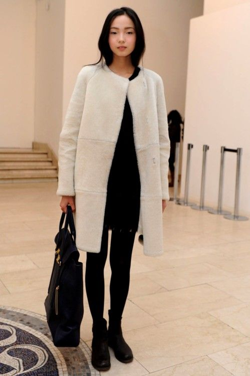 Zwart jurkje en korte laarsjes en witte jas.