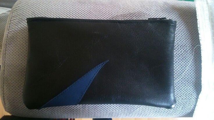 Pochette cuir bicolore doublée avec le tissu des sacs de shopping pour etre lavable. Motif cuir cousu a la machinr dessus.