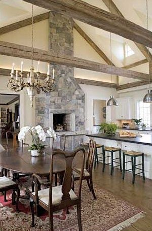 Fireplace in kitchen, larger raised hearth, beams.