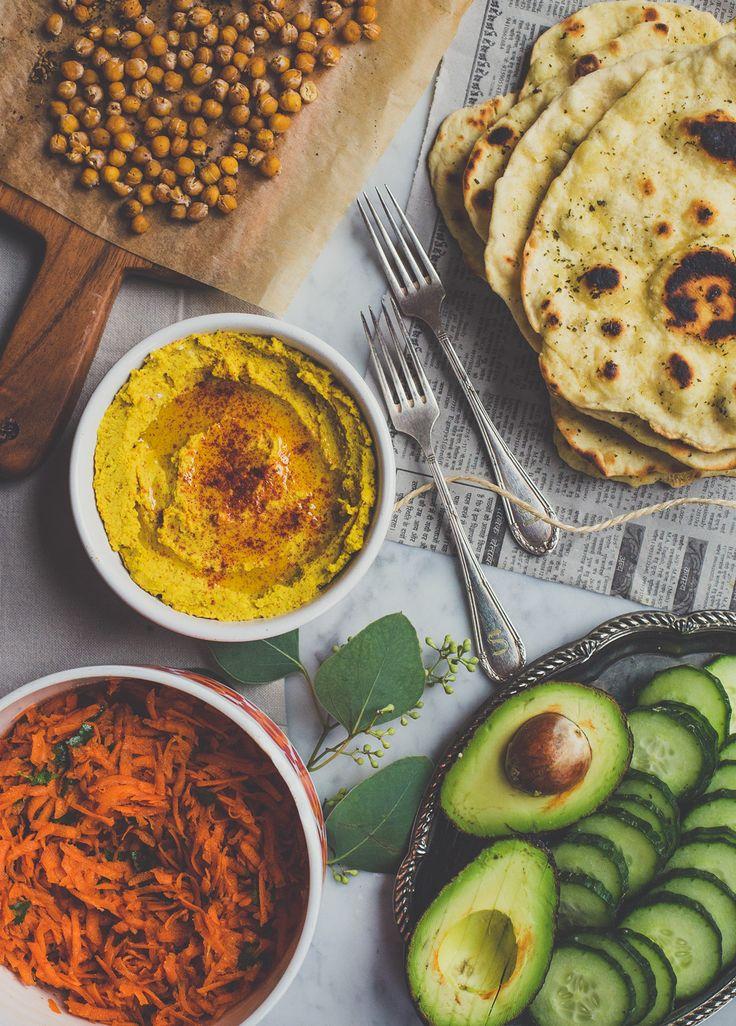 Homemade naan met kerriehummus, geroosterde kikkererwten, wortelsalade en andere veggies.