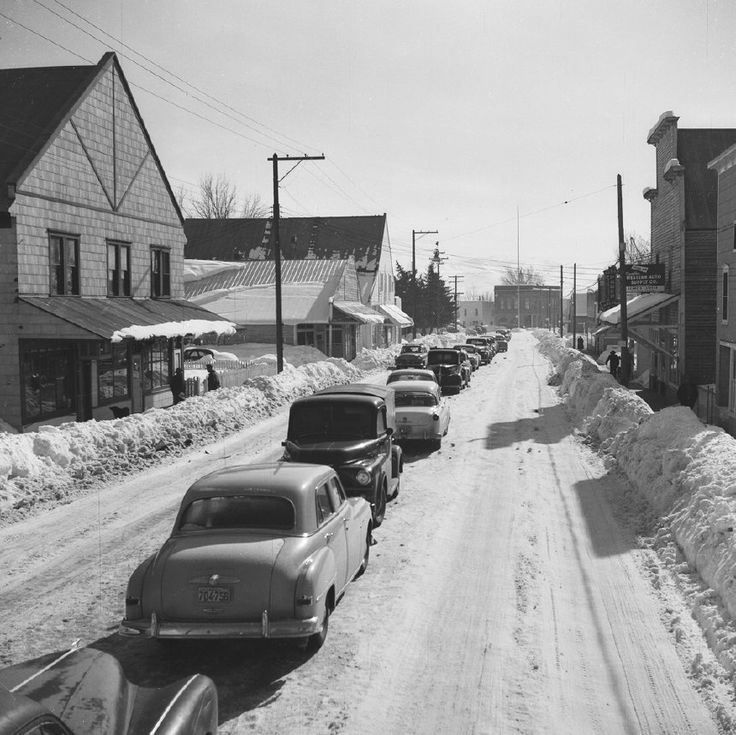 Halfway, OR in winter, 1953. Vehicles parked in middle of street, leaving room for snow plow.