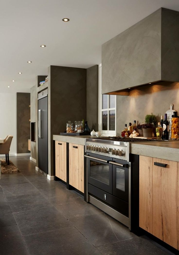Kitchen in wood and concrete with a large double oven stove