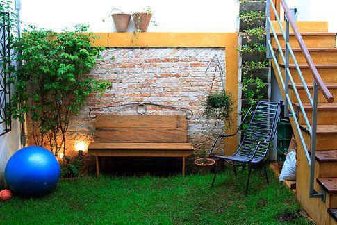 Jardim da casa de vila, com acesso por escada de concreto. Parede de tijolo aparente. Banco de madeira. Gramado, vasos e jardim vertical.