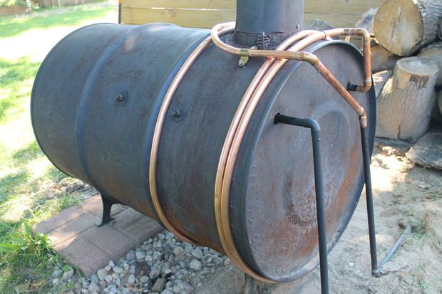 Outdoor wood burning stove. If that copper coil were connected to a coil/fan contraption inside the garage as a radiator, could avoid the risk of poor combustion and fire risk inside the garage, but still heat the garage easily.