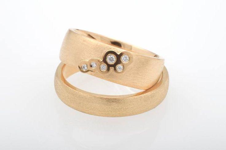 Keltakultaiset kihlasormukset. Naisen sormuksessa kuplivat timantit.