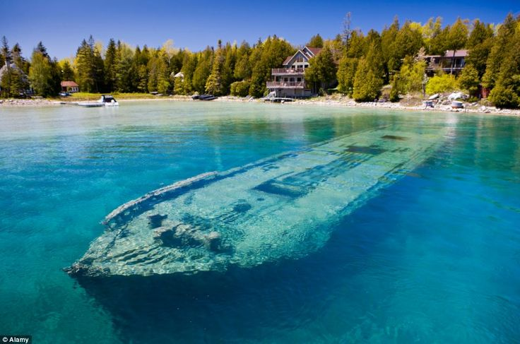The hull of Sweepstakes lies just twenty feet below clear blue water of Ontario lake where it sank in 1885