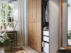 Vestíbulo pequeño con un armario PAX con puertas correderas HURDAL de pino macizo y una mesa ARKELSTORP verde.