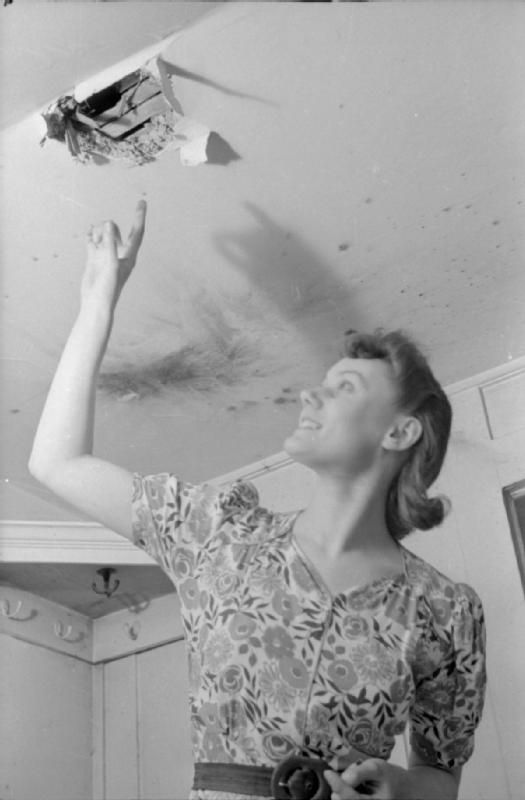 A DAY IN THE LIFE OF A WARTIME HOUSEWIFE: EVERYDAY LIFE IN LONDON, ENGLAND, 1941. Mrs Day points to a hole in the ceiling where a fire bomb recently came through into her South Kensington home. Scorch marks can be seen on the ceiling next to the hole.