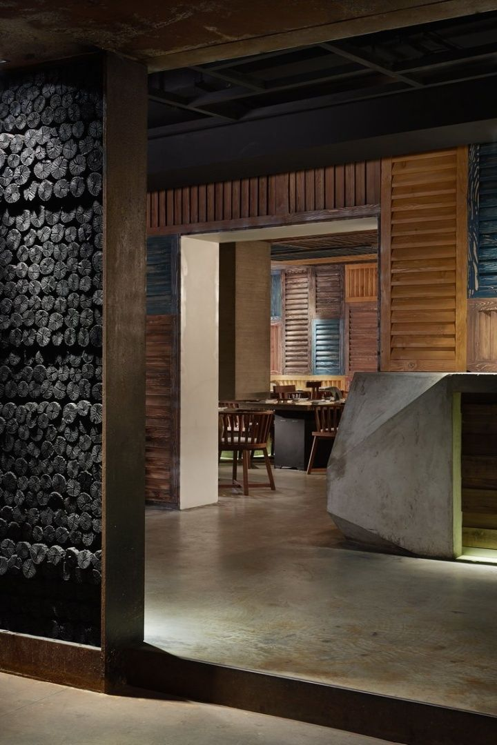 Yakiniku Master restaurant by Golucci International Design, Shanghai -- The recycled wood pieces are reshaped and used to decorate the red bricks, presenting a mottled color wall, coupled with charcoal that has been used in previous stores, demonstrating the image and characteristics of yakiniku (Japanese BBQ).