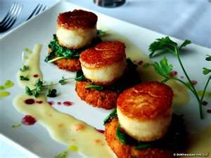 Plump tender sea scallops set a top panko crusted crab cakes in a base of wasabi coconut sauce