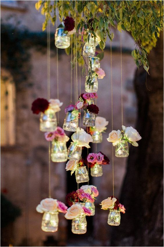 Rustic and regal summer wedding decorations. Dainty jars are filled with LED lights and delicate flowers, perfect for creating an intimate atmosphere.