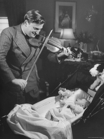 Violinist Yehudi Menuhin, playing the violin for his baby daughter