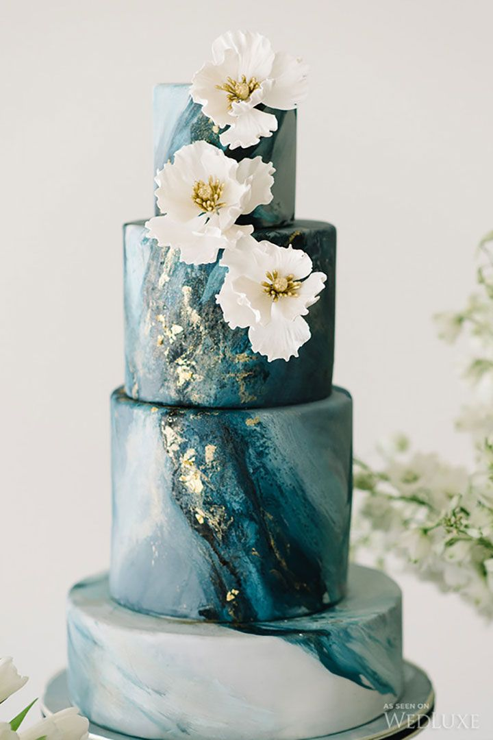 4 tier blue marble with white sugar flowers and gold leaf.