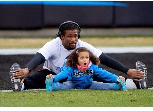DeAngelo Williams stretching with his daughter on the field.