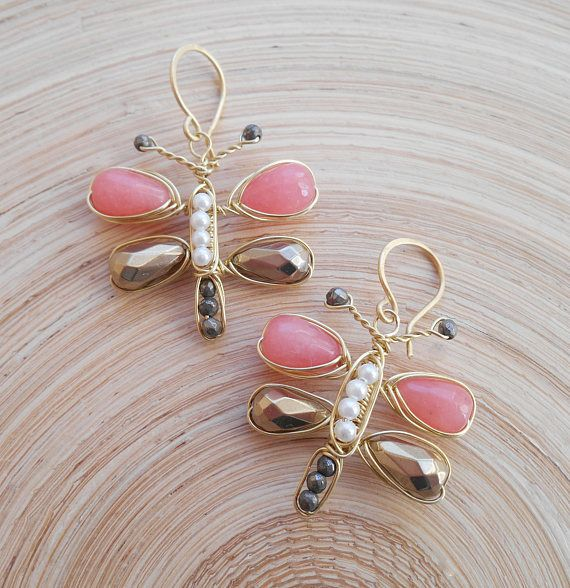 Echoing the delicate features of a butterfly, Asterope gemstone wire wrapped earrings are hand-crafted with gold filled wire and gemstones, including: strawberry jade faceted drop briolettes, gold hematite faceted drop briolettes, freshwater pearls and gray gold pyrite faceted
