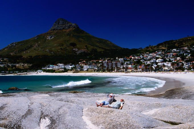 Sunbathers with Clifton Bay, Cape Town  Sunbathers with Clifton Bay in background. South Africa.