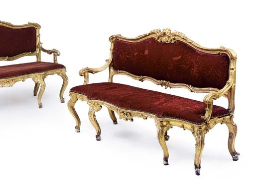 A PAIR OF PIEDMONTESE GILTWOOD DIVANI  TURIN, CIRCA 1750  Each with a cartouche shaped back and serpentine seat-rail centred by rocaille clasps with red velvet upholstery, the downswept arms above rocaille-headed cabriole legs. FROM THE COLLECTION OF S.A.R. LA PRINCIPESSA REALE MARIA GABRIELLA DI SAVOIA.