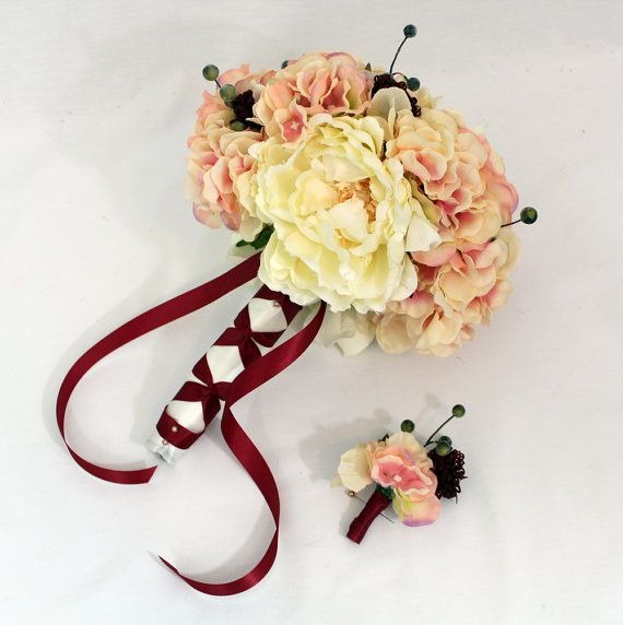 I like the gorgeous deep red ribbon that wraps around the base of the bouquet and cascades down the brides hands =)