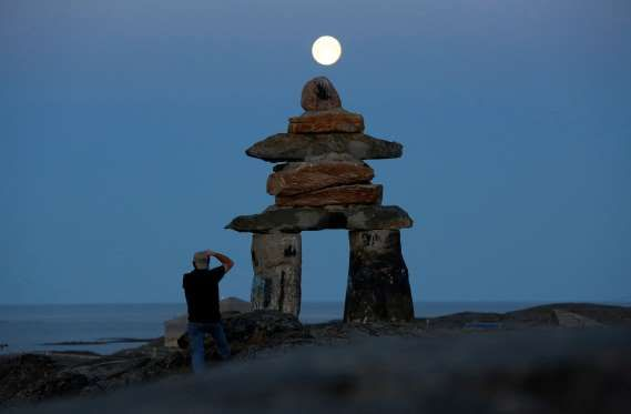 A man photographs a giant inukshuk as the moon rises above it in Rankin Inlet, Nunavut Aug. 21, 2013. The inukshuk is a stone landmark or cairn used by the Inuit people in the arctic.
