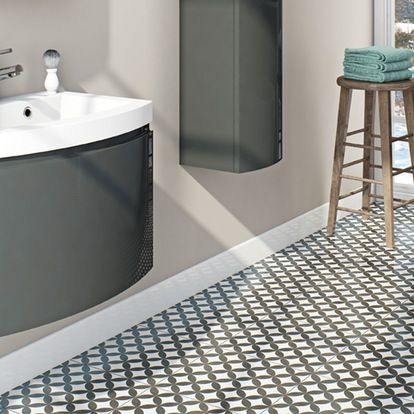 close up of circle patterned floor tiles with black bathroom furniture and wooden stool