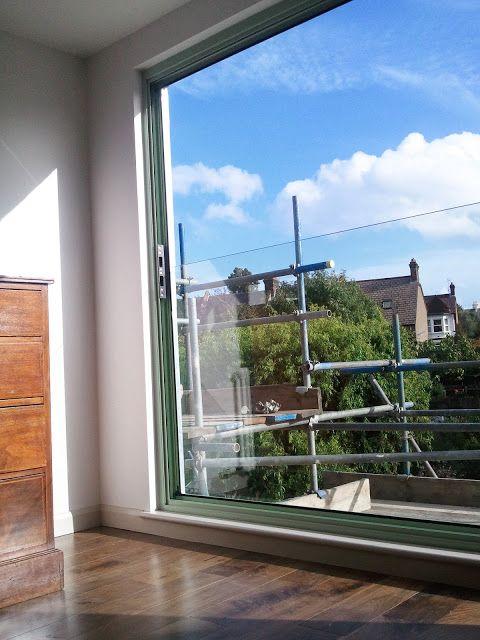 Loft extension, London, by Southstudio.  Full-height sliding-folding door with glass balustrade.