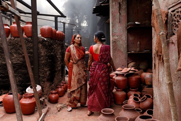 © Maja Bednas / National Geographic Traveler Photo Contest. 2015. People in Dharavi slum in Mumbai work hard, producing mostly recycled articles and pottery. The posture of these two women at the local pottery store, taking a short break for conversation, express dignity, while the colours of their saris perfectly blend with the scenery.