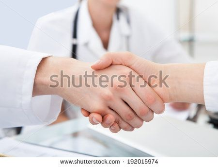 cropped image of doctors shaking hands at desk in clinic