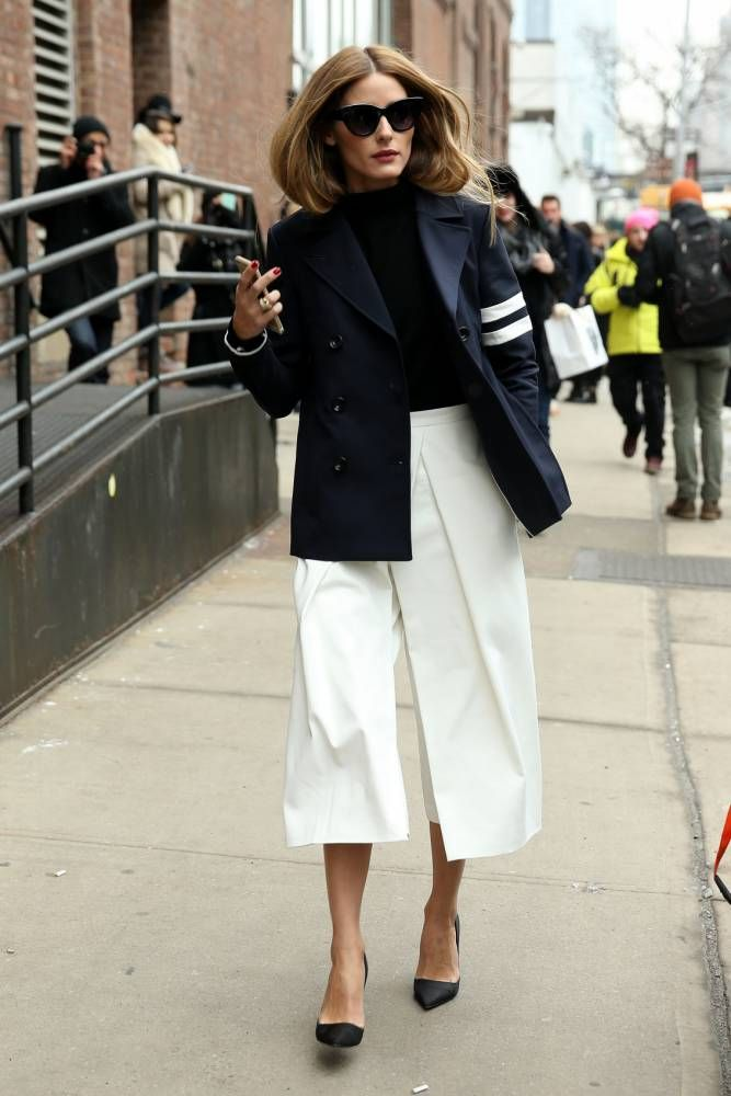 Olivia Palermo, wearing white culotte pants with a navy blazer attends the Tibi fashion show on February 14, 2015 in New York City.