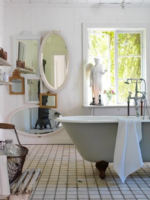 Belle salle de bain blance, originale avec la fenêtre et le bain sur pied. J'aime les miroirs.