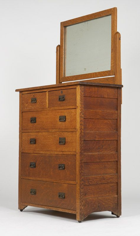 L & JG Stickley Oak Chest of Drawers. Early 20th century, lacking signature, the pivoting rectangular mirror attached to pointed rectangular uprights rising from the rectangular top, over two short drawers above four long drawers, with patinated metal hardware.