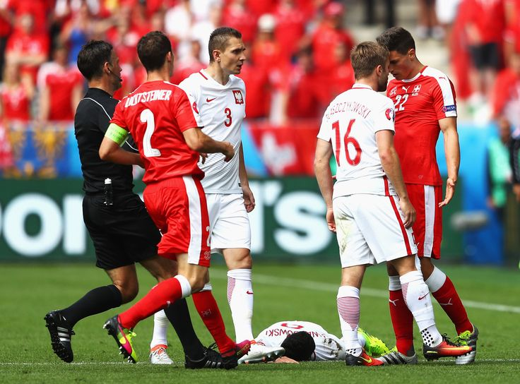 Fabian Schaer (1st R) of Switzerland and Jakub Blaszczykowski (2nd R) of Poland argue after Schaer's foul to Robert Lewandowski of Poland during the UEFA EURO 2016 round of 16 match between Switzerland and Poland at Stade Geoffroy-Guichard on June 25, 2016 in Saint-Etienne, France.