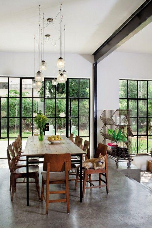 כיסאות פינת האוכל נאספו בבית כנסת ישן. שולחן בעל משטח עץ ורגלי מתכת שחורות מתכתב עם פרופיל הברזל של החלונות ויוצר אחידות סגנונית. צילום: בועז לביא