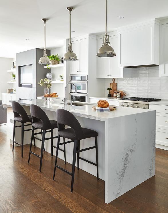 Three Dark Gray Velvet Stools Sit At A White Kitchen Island Fitted With A Calcutta Quartz Waterfall Co White Kitchen Island Kitchen Design Waterfall Countertop