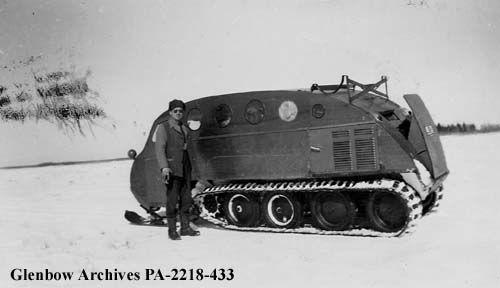 Mar 1950 Constable M. G. Crawford beside snowmobile, Dinner Point, Cumberland Lake, Saskatchewan.