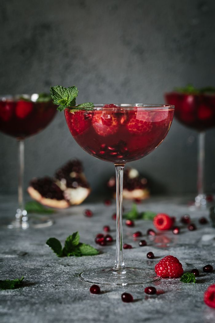 Raspberry and Pomegranate Rosé Summer Cocktail - This recipe is made with mint infused honey simple syrup, gin, pomegranate juice, and sparkling rosé. It is served with fresh raspberries, pomegranate seeds, and mint. It is such an impressive cocktail for any summer gathering.