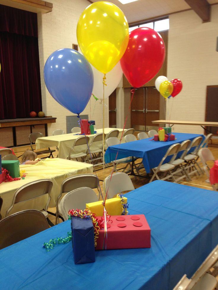 Centros de mesa para fiesta lego con cajas de que lucen como piezas Lego y globos atados a estas. #FiestaLego