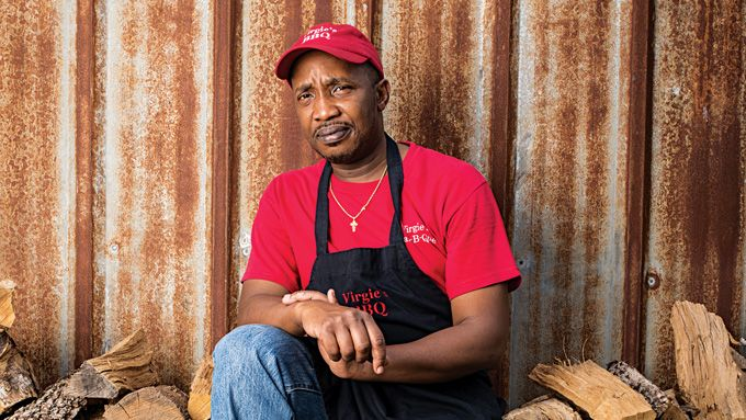 Pitmaster Adrian Handsborough, of Virgie's Bar-B-Que, in Houston, perched on his pile of oak.