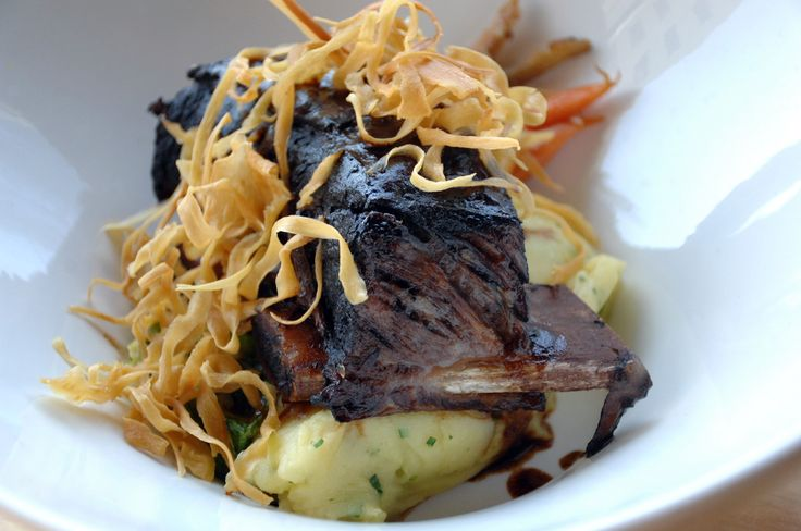 Braised Beef Short Ribs with saute brussel sprout leaves, heirloom baby carrots, roasted garlic truffle mashed potatoes garnish with parsnip chips