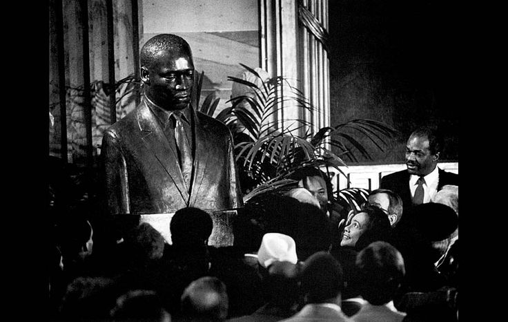 Jan. 16, 1986: Coretta Scott King, wife of Martin Luther King Jr., lower right, gazes up at a 3-foot tall bronze bust of her late husband, after the unveiling ceremony in the Capitol.