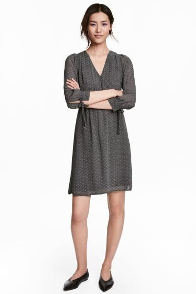 Short woven dress with a wrapover front with a covered button and decorative gathers at the shoulders. 3/4-length sleeves with narrow cuffs with a tie and a