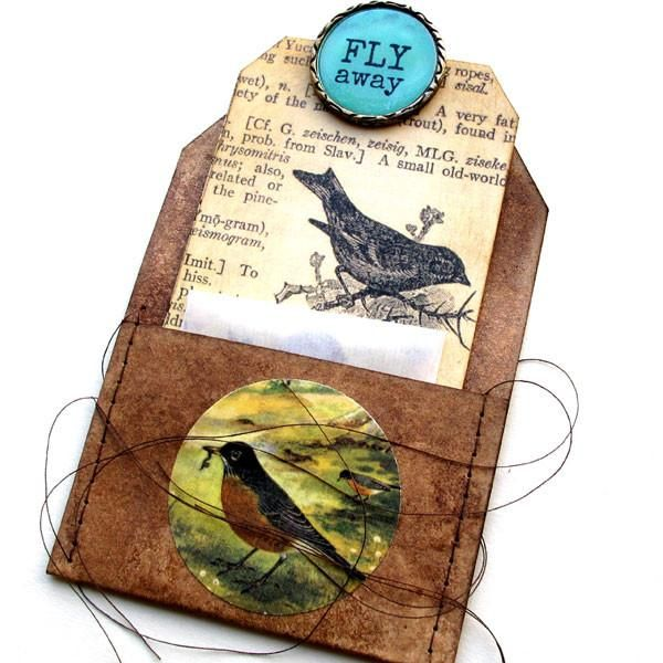 """Fly Away Bird Stitched Pocket Tag The pocket tag is hand dyed with walnut ink and embellished with a paper bird circle. The tag is stitched to create a pocket. There is 1 collage bird tag that fits inside of the pocket tag. The tag is embellished a glassine envelope, hand stamped small bird tag, vintage bird images, and a Fly Away metal epoxy circle.The size of the stitched pocket tag is 3"""" x 4"""" and the size of the other tag is approximately 2-1/2"""" x 4-3/4"""". Th..."""
