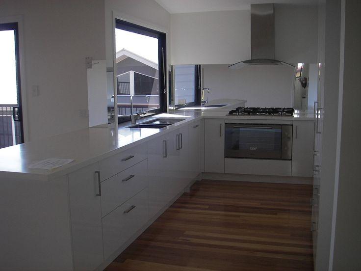 Modern all white Kitchen with mirror splashback + timber flooring   Tru-Built Builders Queendsland