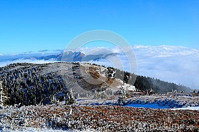 Great Fatra (Velká Fatra) mountain in Slovakia in early winter. View from the mountains ridge - sunny day with a touch of snow and clouds below the mountains.