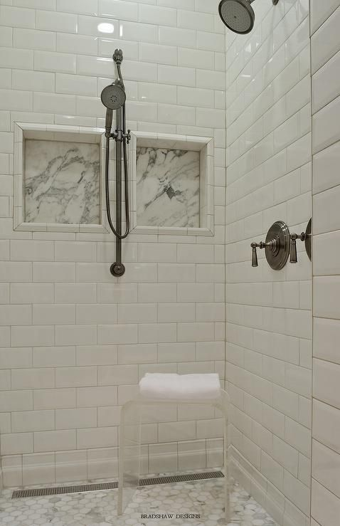Fantastic walk in shower features walls clad in white beveled subway tiles fitted with marble shower niches lined with satin nickel shower heads and a acrylic waterfall stool atop a marble hex shower floor.
