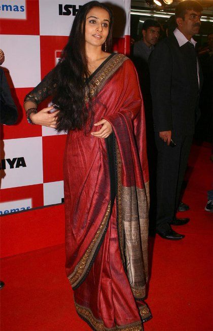 Red, gold, and black saris on Vidya Balan